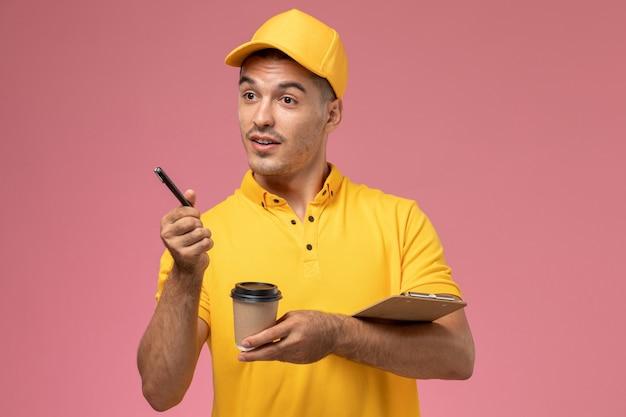 Männlicher kurier der vorderansicht in der gelben uniform, die die kaffeetasse und den notizblock hält, die notizen auf dem rosa schreibtisch aufschreiben