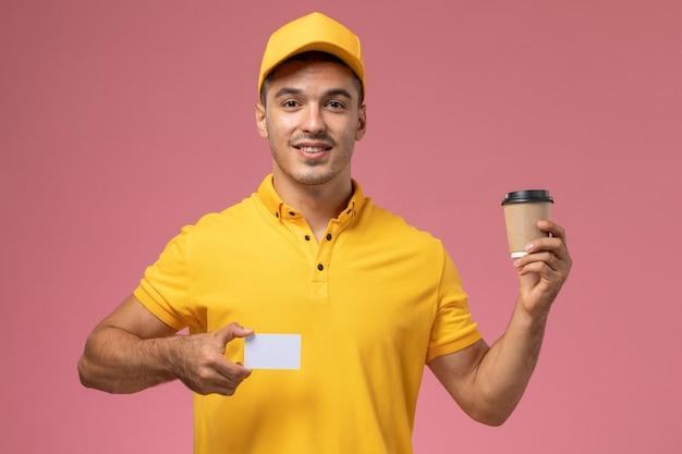 Männlicher kurier der vorderansicht in der gelben uniform, die die kaffeetasse und die karte der lieferung auf rosa hintergrund hält