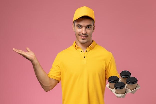 Männlicher kurier der vorderansicht in der gelben uniform, die die kaffeetassen der lieferung auf dem rosa schreibtisch lächelt und hält