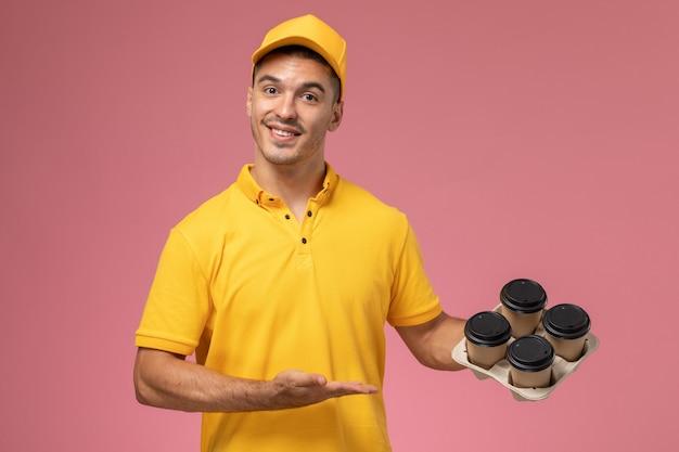 Männlicher kurier der vorderansicht in der gelben uniform, die die kaffeetassen der lieferung auf rosa hintergrund lächelt und hält