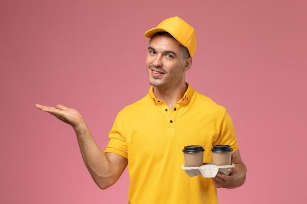 Männlicher kurier der vorderansicht in der gelben uniform, die die kaffeetassen der lieferung hält, die auf hellrosa schreibtisch lächeln