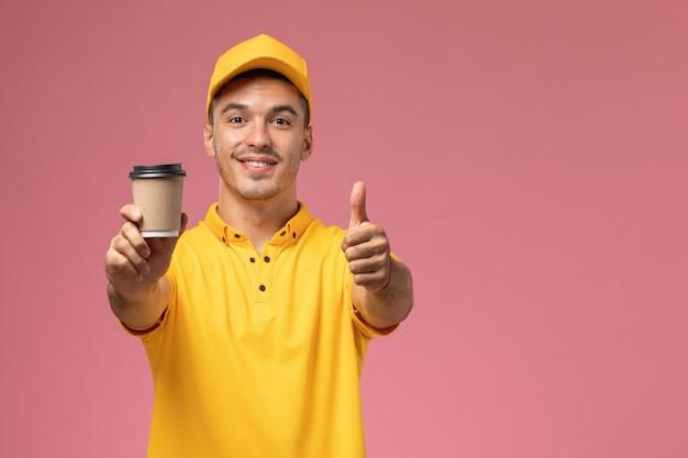 Männlicher kurier der vorderansicht in der gelben uniform, die kaffee-lieferbecher mit lächeln auf dem rosa hintergrund hält