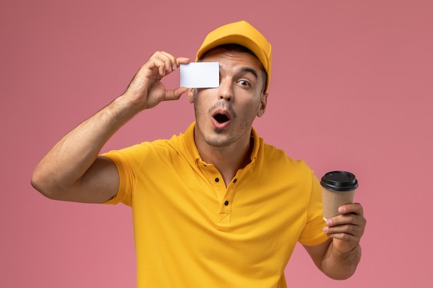 Männlicher kurier der vorderansicht in der gelben uniform, die kaffeetasse und karte der lieferung auf rosa schreibtisch hält