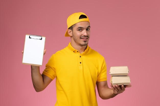 Männlicher kurier der vorderansicht in der gelben uniform, die kleine nahrungsmittelpakete auf rosa hintergrund hält.