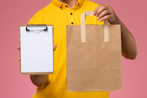 Männlicher kurier der vorderansicht in der gelben uniform, die kleinen notizblock und liefernahrungsmittelpaket auf dem rosa hintergrund hält.