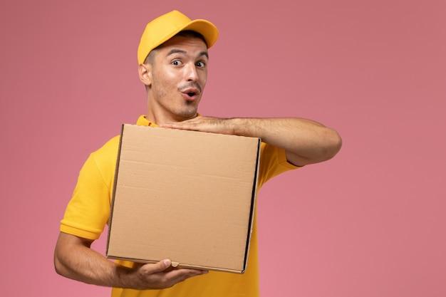 Männlicher kurier der vorderansicht in der gelben uniform, die lebensmittel-lieferbox mit lustigem ausdruck auf dem rosa schreibtisch hält