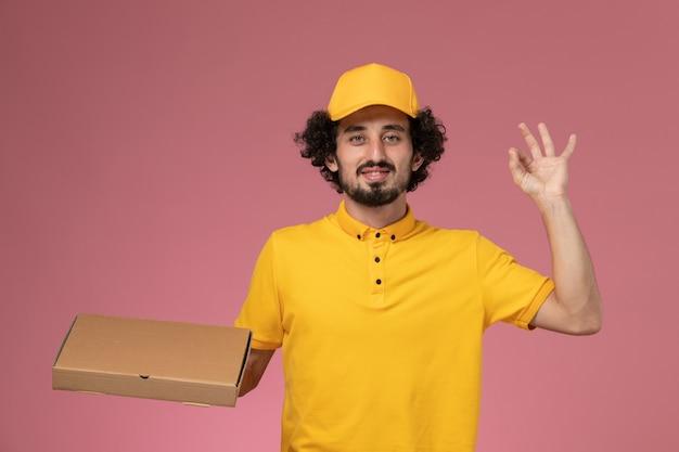 Männlicher kurier der vorderansicht in der gelben uniform, die lebensmittelabgabebox an der hellrosa wand hält