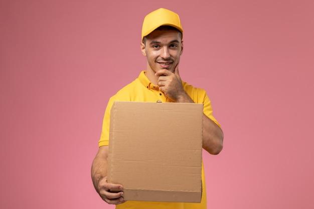 Männlicher kurier der vorderansicht in der gelben uniform, die lebensmittelabgabebox auf dem hellrosa hintergrund hält und öffnet