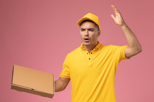 Männlicher kurier der vorderansicht in der gelben uniform, die lebensmittelabgabebox auf dem rosa hintergrund hält
