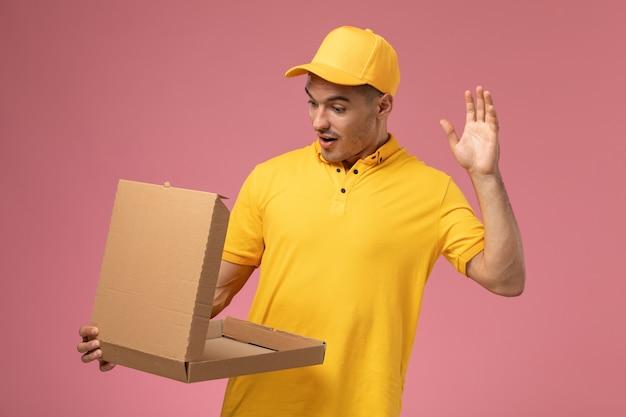 Männlicher kurier der vorderansicht in der gelben uniform, die lebensmittelabgabebox auf hellrosa schreibtisch hält und öffnet