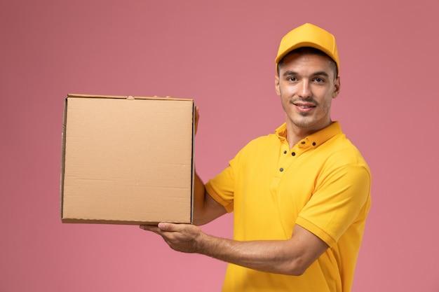 Männlicher kurier der vorderansicht in der gelben uniform, die lebensmittelabgabebox posign mit ihm auf dem rosa hintergrund hält