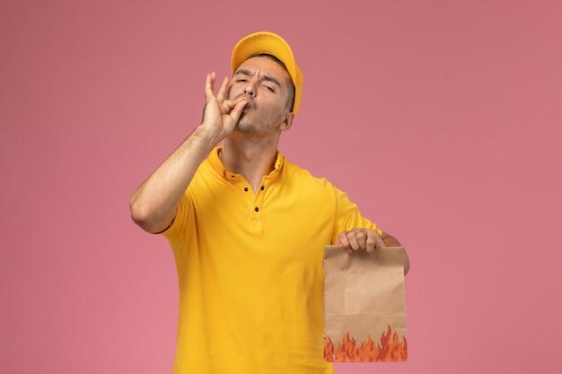 Männlicher kurier der vorderansicht in der gelben uniform, die lebensmittelpaket hält, das schmackhaftes zeichen auf rosa hintergrund zeigt