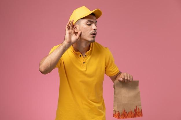 Männlicher kurier der vorderansicht in der gelben uniform, die lebensmittelpaket hält, das versucht, auf dem rosa hintergrund zu hören