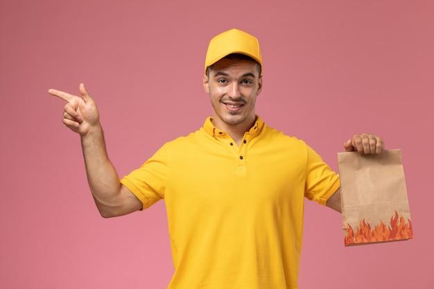 Männlicher kurier der vorderansicht in der gelben uniform, die lebensmittelpaket mit leichtem lächeln auf rosa hintergrund hält