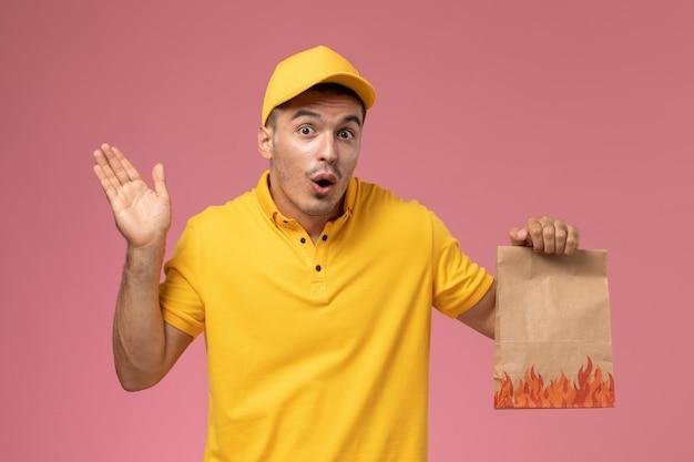 Männlicher kurier der vorderansicht in der gelben uniform, die lebensmittelpaket mit überraschtem ausdruck auf dem rosa hintergrund hält
