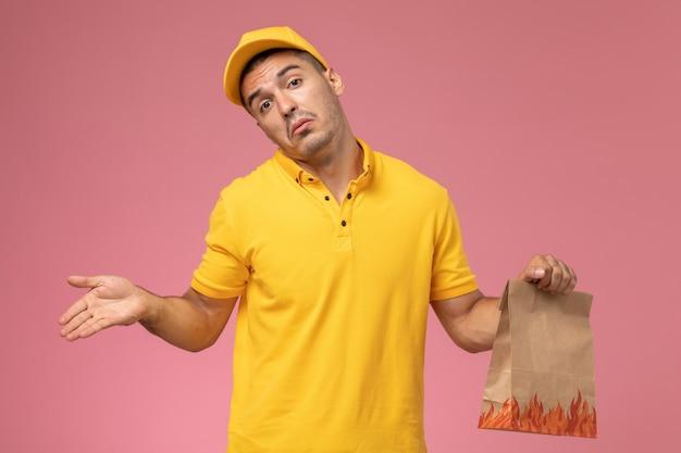 Männlicher kurier der vorderansicht in der gelben uniform, die lebensmittelpaket mit verwirrtem ausdruck auf dem rosa hintergrund hält