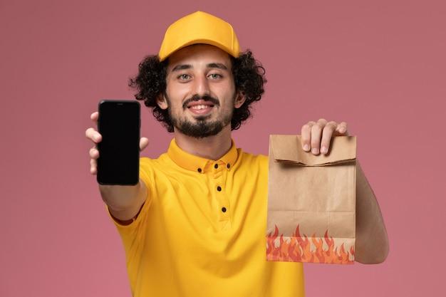 Männlicher kurier der vorderansicht in der gelben uniform, die lebensmittelpaket und smartphone an der rosa wand hält