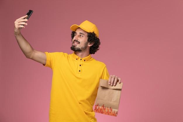 Männlicher kurier der vorderansicht in der gelben uniform, die lebensmittelverpackung hält und foto auf der rosa wand macht
