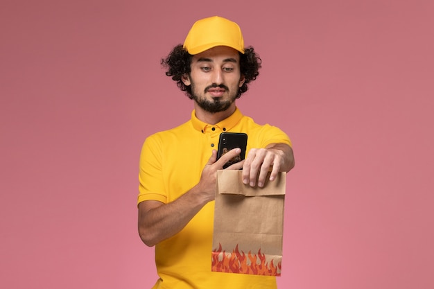 Männlicher kurier der vorderansicht in der gelben uniform, die lebensmittelverpackung hält und foto davon auf der rosa wand macht