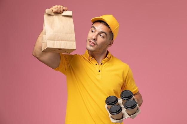 Männlicher kurier der vorderansicht in der gelben uniform, die lebensmittelverpackung und lieferkaffeetassen auf hellrosa hintergrund hält