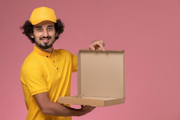 Männlicher kurier der vorderansicht in der gelben uniform, die leere nahrungsmittelbox auf hellrosa wand hält