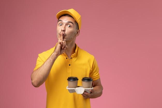 Männlicher kurier der vorderansicht in der gelben uniform, die lieferkaffeetassen hält, die bitten, auf hellrosa hintergrund ruhig zu sein