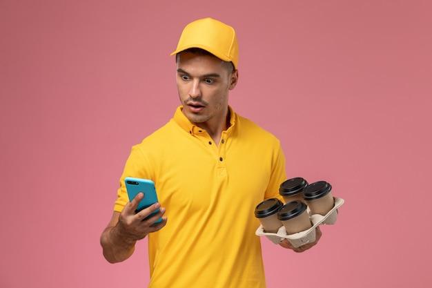 Männlicher kurier der vorderansicht in der gelben uniform, die lieferkaffeetassen hält, während sein telefon auf dem rosa hintergrund verwendet wird