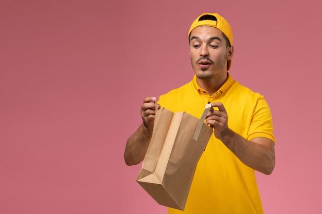 Männlicher kurier der vorderansicht in der gelben uniform, die lieferpapierpaket auf dem hellrosa schreibtisch hält.