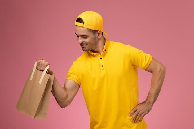 Männlicher kurier der vorderansicht in der gelben uniform, die lieferpapierpaket auf hellrosa hintergrund hält.