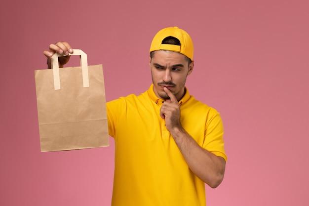 Männlicher kurier der vorderansicht in der gelben uniform, die lieferpapierpaket denkt, das auf dem hellrosa hintergrund denkt.