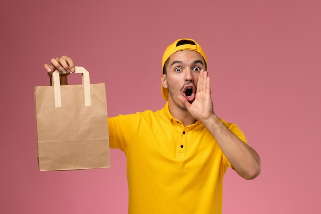 Männlicher kurier der vorderansicht in der gelben uniform, die lieferpapierpaket hält, das auf hellrosa hintergrund ruft.