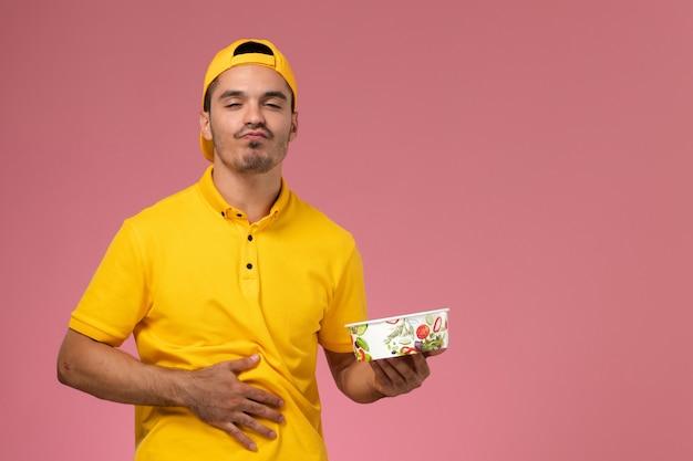 Männlicher kurier der vorderansicht in der gelben uniform, die lieferschüssel hält, die seinen magen auf dem rosa hintergrund berührt.