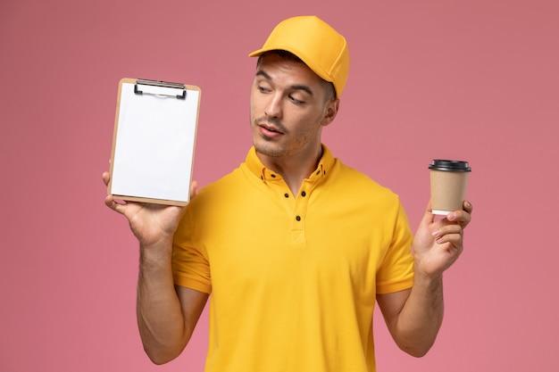Männlicher kurier der vorderansicht in der gelben uniform, die lieferung kaffeetasse und notizblock auf dem rosa hintergrund hält