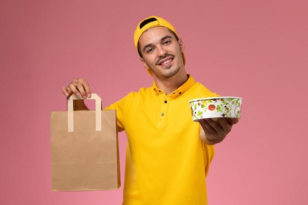 Männlicher kurier der vorderansicht in der gelben uniform, die lieferung lebensmittelverpackungsschüssel auf rosa hintergrund hält.