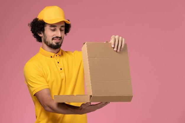 Männlicher kurier der vorderansicht in der gelben uniform, die nahrungsmittelbox auf hellrosa wand hält
