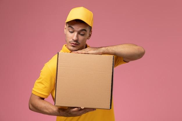 Männlicher kurier der vorderansicht in der gelben uniform, die nahrungsmittellieferbox auf rosa schreibtisch hält