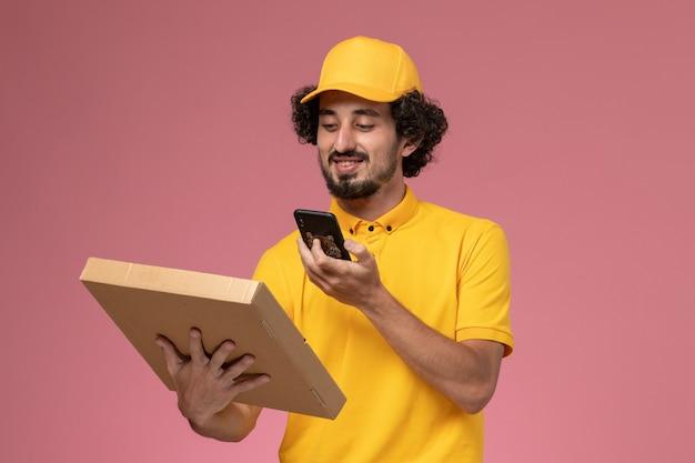 Männlicher kurier der vorderansicht in der gelben uniform, die nahrungsmittellieferbox hält, die ein foto davon auf rosa wand macht