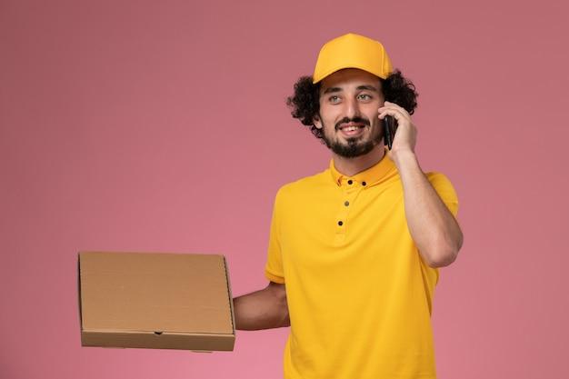 Männlicher kurier der vorderansicht in der gelben uniform, die nahrungsmittellieferbox hält und am telefon auf der hellrosa wand spricht
