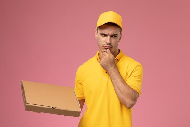 Männlicher kurier der vorderansicht in der gelben uniform, die nahrungsmittellieferbox hält und auf dem rosa hintergrund denkt