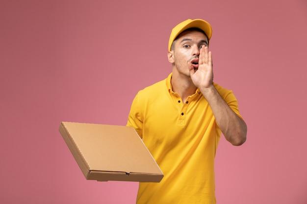 Männlicher kurier der vorderansicht in der gelben uniform, die nahrungsmittellieferbox hält und jemanden auf dem rosa hintergrund ruft