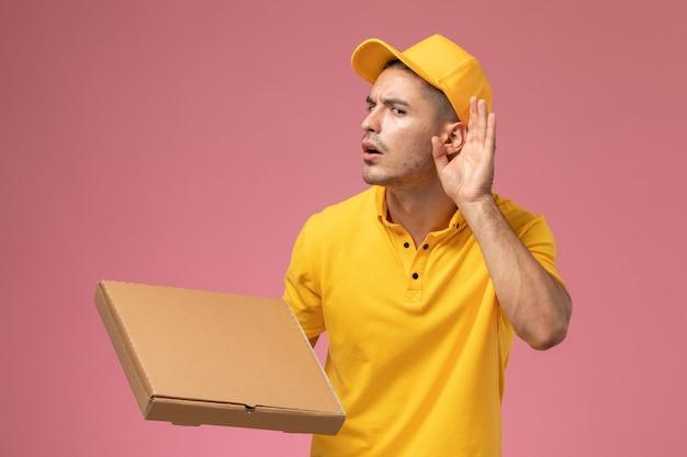 Männlicher kurier der vorderansicht in der gelben uniform, die nahrungsmittellieferbox hält und versucht, auf dem rosa hintergrund zu hören