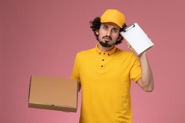 Männlicher kurier der vorderansicht in der gelben uniform, die nahrungsmittellieferbox und notizblock denkt auf rosa wand hält