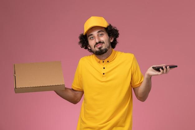 Männlicher kurier der vorderansicht in der gelben uniform, die nahrungsmittellieferbox und sein telefon an der rosa wand hält