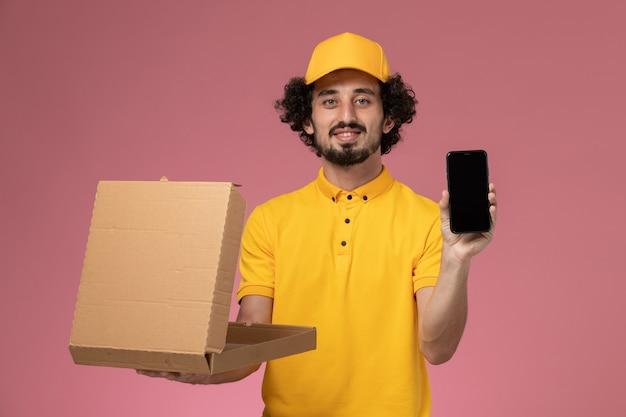 Männlicher kurier der vorderansicht in der gelben uniform, die nahrungsmittellieferbox und telefon an der hellrosa wand hält