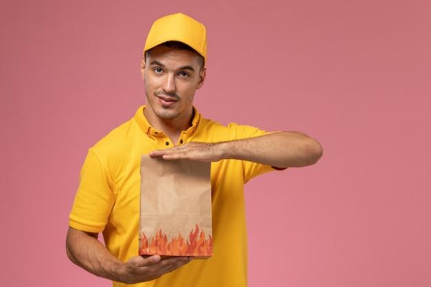 Männlicher kurier der vorderansicht in der gelben uniform, die nahrungsmittelpaket auf rosa hintergrund hält