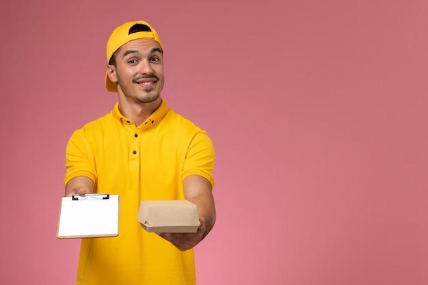 Männlicher kurier der vorderansicht in der gelben uniform, die notizblock und kleines nahrungsmittelpaket auf rosa wand hält