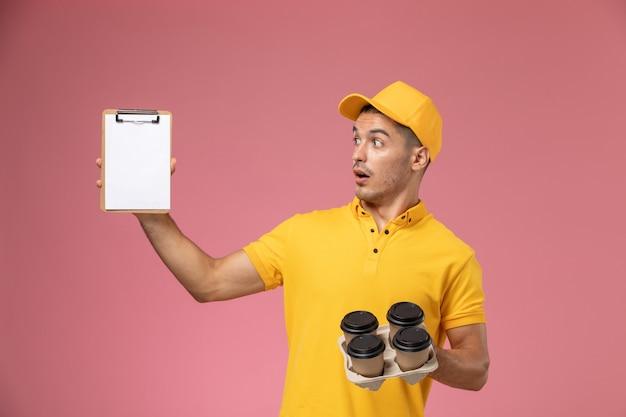 Männlicher kurier der vorderansicht in der gelben uniform, die notizblock und lieferkaffeetassen auf dem hellrosa schreibtisch hält