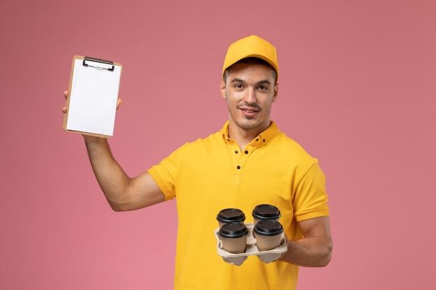 Männlicher kurier der vorderansicht in der gelben uniform, die notizblock und lieferkaffeetassen auf rosa schreibtisch hält