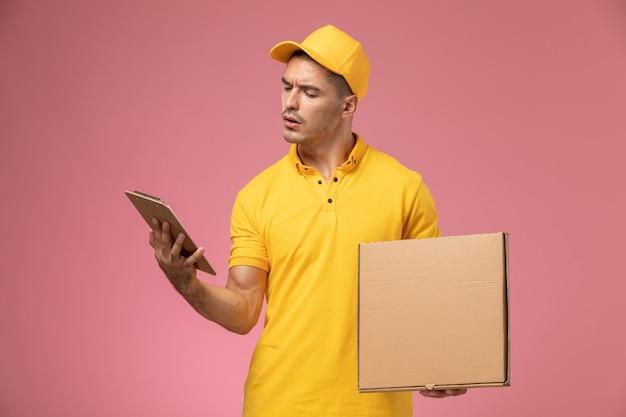 Männlicher kurier der vorderansicht in der gelben uniform, die notizblock und nahrungsmittellieferbox auf dem rosa hintergrund hält