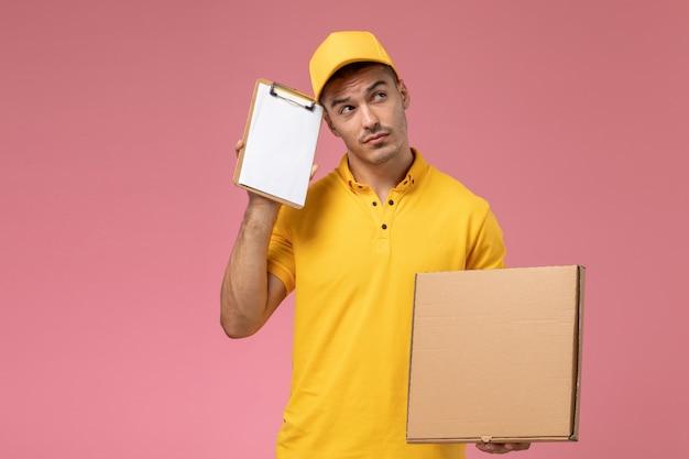 Männlicher kurier der vorderansicht in der gelben uniform, die notizblock zusammen mit dem lebensmittellieferkasten denkt, der auf dem rosa hintergrund denkt